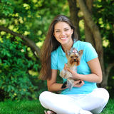 Beautiful smiling young woman with small dog, against green of s. Beautiful smiling young woman with small dog Royalty Free Stock Images