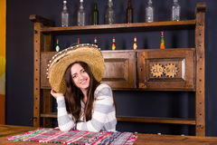 Beautiful smiling young woman in a sombrero leaned on bar counte. R in Mexican pub, a shelf with spicy sauces and empty bottles in the background royalty free stock images