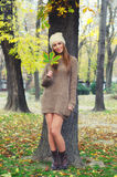 Beautiful smiling young woman standing in the autumn forest Royalty Free Stock Image