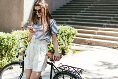 Beautiful smiling young woman in sugnlasses using smartphone while standing with bike. On street stock photo