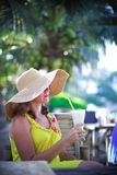 Beautiful smiling young woman in sunglasses wearing hat with a cocktail at the beach cafe stock image