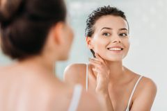 Beautiful smiling young woman touching skin and looking at mirror. In bathroom stock photography