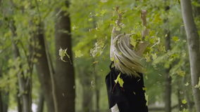Beautiful smiling young woman walking in a park, throwing up autumn maple leaves stock footage