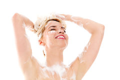 Beautiful smiling young woman washing her hair with shampoo - isolated on white. Royalty Free Stock Photo