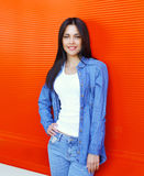 Beautiful smiling young woman wearing a blue jeans clothes over red Royalty Free Stock Images