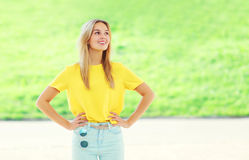 Beautiful smiling young woman wearing a colorful yellow t-shirt Royalty Free Stock Images