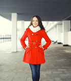 Beautiful smiling young woman wearing a red coat and scarf Stock Photos