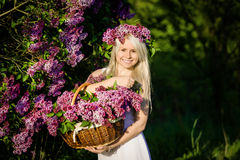 Beautiful smiling young woman is wearing wreath of lilac flowers Stock Photos