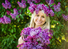 Beautiful smiling young woman is wearing wreath of lilac flowers Stock Photography