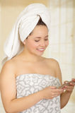 Beautiful smiling young woman with a white towel covering her head is using her cellphone Royalty Free Stock Images