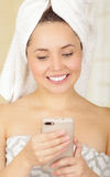 Beautiful smiling young woman with a white towel covering her head is using her cellphone Royalty Free Stock Photography