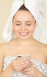 Beautiful smiling young woman with a white towel covering her head is using her cellphone Stock Photo