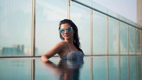 Beautiful smilling girl in sunglasses in the pool stock video