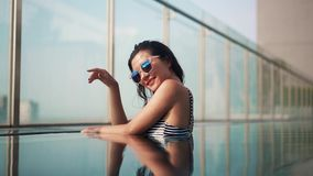 Beautiful smilling girl in sunglasses in pool stock footage