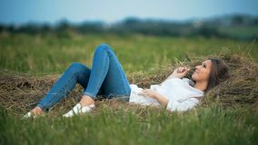 Beautiful smilling woman lies in the golden straw grass stock video