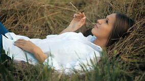 Beautiful smilling woman lies in the golden straw grass stock footage