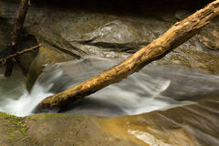 Beautiful smooth flowing stream with a small waterfall Stock Image