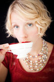 Beautiful Snobbish lady drinking tea. Beautiful lady with an old fashioned style shot in studio with a black background royalty free stock photography