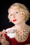 Beautiful Snobbish lady holding a cup of tea. Beautiful lady with an old fashioned style shot in studio with a black background stock photography