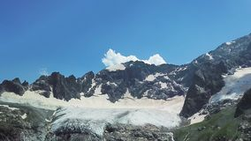 Beautiful snow-capped mountains against the blue sky. Top view of top of mountain with snow cap stock footage