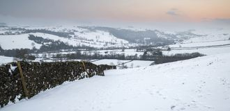 Beautiful snow covered Winter landscape at sunrise in Peak Distr. Snow covered Winter landscape at sunrise in Peak District in England Royalty Free Stock Photos