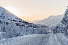 Beautiful snow covered winter road with road sign and trees in mountains,. Kolyma highway stock images