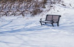 Beautiful snow covered winter scene with bench royalty free stock photo