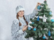 Beautiful snow girl is decorating a Christmas tree. New Year and Christmas. royalty free stock photos