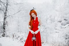 Beautiful snow maiden girl with red hair on december nature. Beautiful redhead retro woman in red dress and with long gloves on royalty free stock images