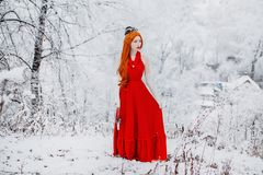 Beautiful snow maiden girl with red hair on fascinating nature. Beautiful redhead retro woman in red gown and with long gloves on. Background of fascinating stock images