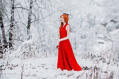 Beautiful snow maiden girl with red hair on february nature. Beautiful redhead retro woman in red dress and with long gloves on royalty free stock photography