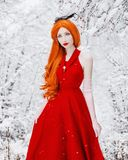 Beautiful snow maiden girl with red hair on winter background. Beautiful redhead retro woman in red dress and with long gloves on stock images
