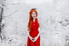 Beautiful snow maiden girl with red hair on winter nature. Beautiful redhead retro woman in red dress and with long gloves on royalty free stock photography