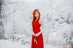 Beautiful snow maiden girl with red hair on winter nature. Beautiful redhead retro woman in red dress and with long gloves on royalty free stock images