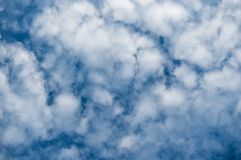 Beautiful snow-white alto-cumulus clouds against a blue sky. Natural background.  stock images