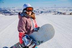 Beautiful snowboarder in Orange glasses with snowboarding. On the mountain slope royalty free stock photo