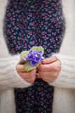 Beautiful snowdrops in hands of a young woman in white cardigan and blues flower dress. Stock Photos