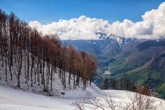 Beautiful snowy Aibga mountain ski slope on cloudy blue sky background at spring dramatic scenic landscape. Royalty Free Stock Image