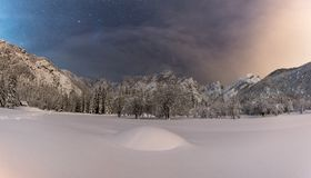 Beautiful snowy field with breathtaking starry sky. And mountains in the background royalty free stock photography