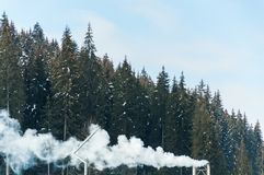 Beautiful snowy mountain forest in boiler plant fumes. Beautiful mountain forest in boiler plant fumes stock photo