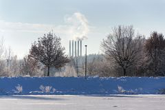 Beautiful snowy romantic winter landscape with smoking chimneys at heating plant among trees, frozen pond in foreground royalty free stock images