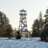 Beautiful snowy winter landscape with watchtower in forest Royalty Free Stock Images