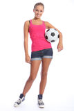 Beautiful soccer player teenage girl with ball. Beautiful soccer player teenage girl with happy smile wearing pink vest and denim shorts, standing with sports Royalty Free Stock Image