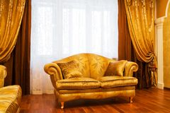Beautiful sofa. At a window in a modern apartment Royalty Free Stock Images