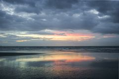 Pastel colored sunset at the dutch beach with reflections in a pool of water royalty free stock photos