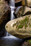 Beautiful soft river waterfall flowing hidden in forest rocks Stock Photo