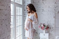 Beautiful soft and sensual pregnant girl in white transparent dr. Ess standing near a window in a bright interior home and smiling Stock Photography