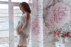Beautiful soft and sensual pregnant girl in white transparent dr. Ess standing near a window in a bright interior home and smiling Stock Images