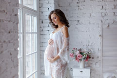 Beautiful soft and sensual pregnant girl in white transparent dr. Ess standing near a window in a bright interior home and smiling Royalty Free Stock Image
