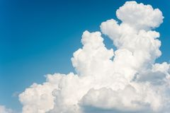 Beautiful soft white fleecy cloud on blue sky background. White soft fleecy cumulus congestus clouds on blue sky background. Vibrant multicolored outdoors Stock Image
